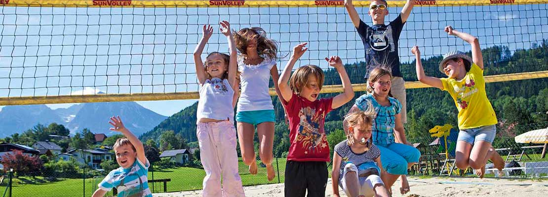 Kinder am Volleyballfeld springen hoch